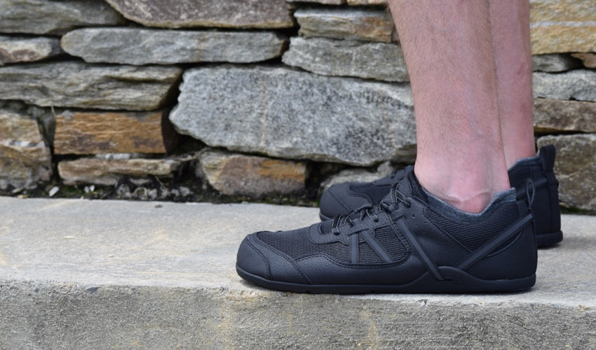 Man in a pair of flat-soled Xero Prio Black athletic shoes standing on a concrete step