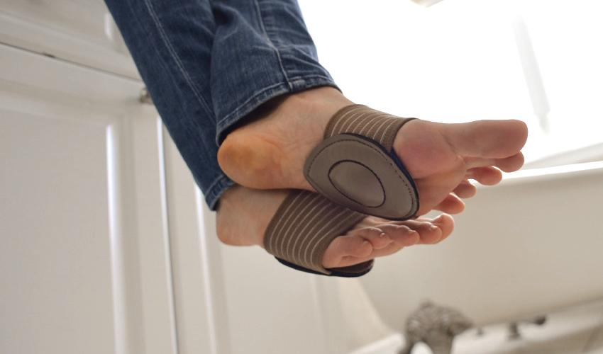 A person wearing Strutz Pro Brown foot pads on bare feet sitting on a bathroom vanity with legs crossed
