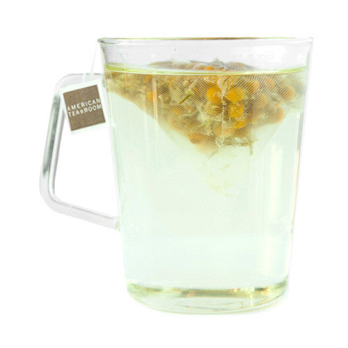 chamomile tea sachet steeping in cup