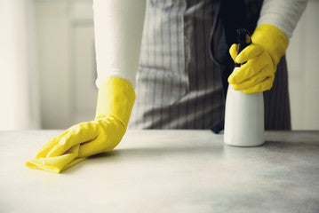 Person cleaning a surface with rubber gloves and disenfectant