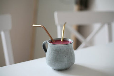 Drink in a handmade ceramic mug with two metal bent straws sticking out on a white tabletop