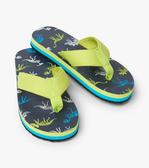 EVA flip flops in navy, lime green and turquoise dinosaur fossils print. Boys flip flops from Hatley.