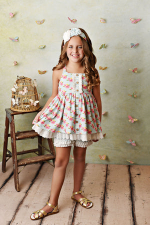 Girls french rose floral print tunic tank with criss cross straps, buttons down front. Eyelet lace trim ruffle. Matching ruffle shorties. Stretch knit fabric. On model.