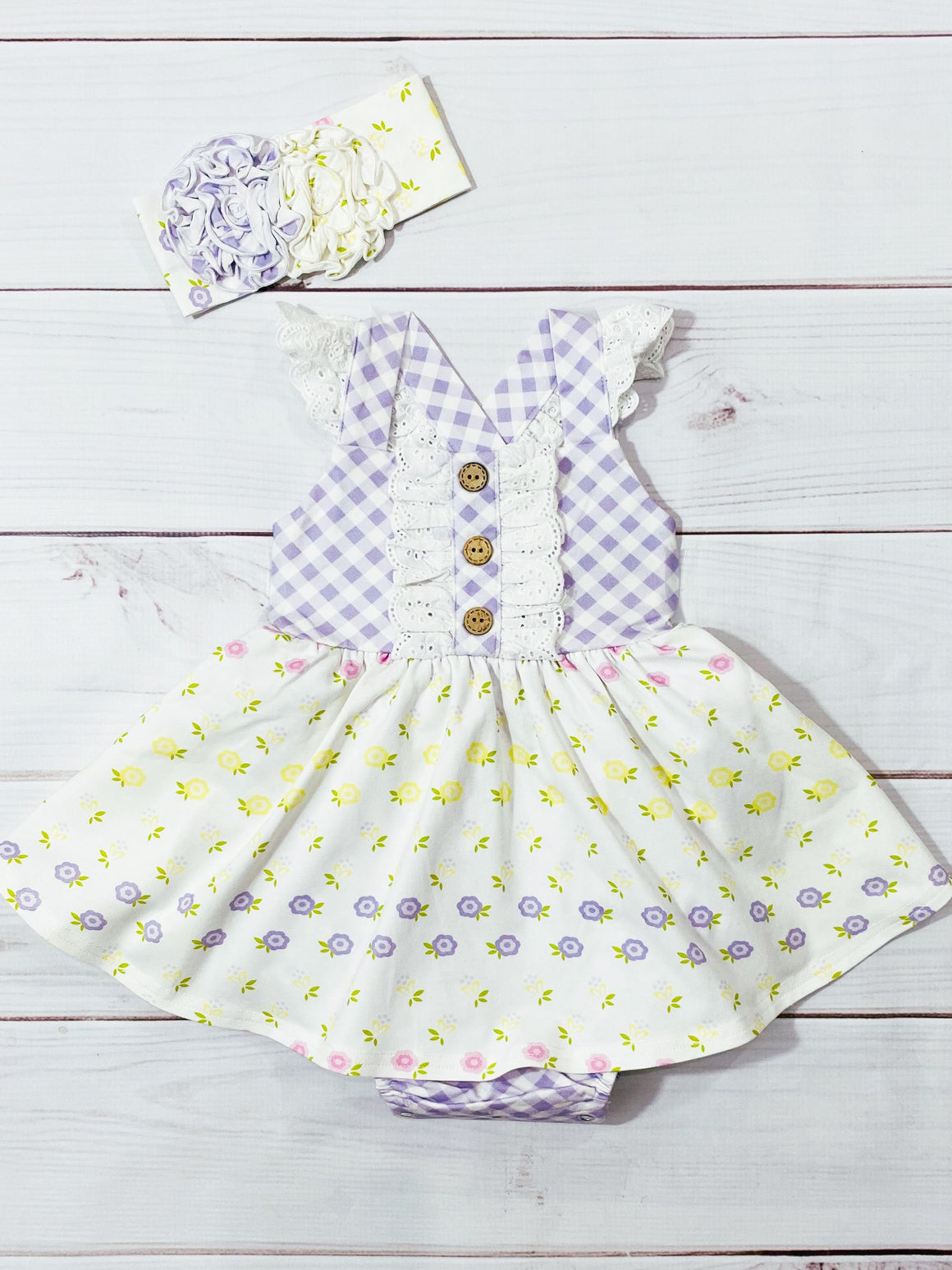 Baby girls lavender gingham flutter sleeve bubble dress in lemon yellow floral with matching headband. Adjustable straps.