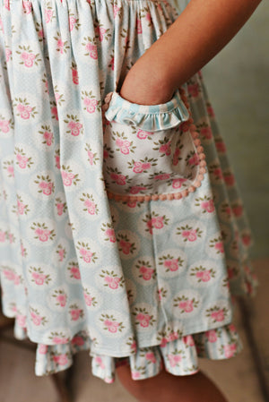 Sweet pale blue and cream stripe knit dress with pink rose floral fabric; double deep ruffle pockets, matching shorties and headband. Close up of pocket.