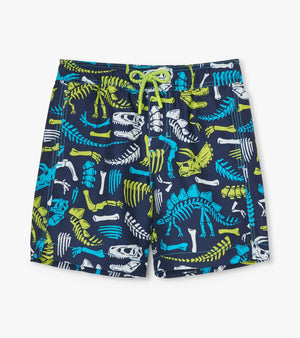 Boys UPF50+ lined quick-dry swim trunks from Hatley. Navy background with lime green, turquoise and white dinosaur fossil bones print. Elastic waistband and functional drawstring tie.