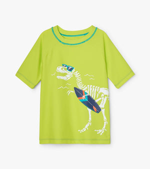Boys quick dry UPF50+ cool dinosaur print short sleeve rashguard. Lime green. Dino wearing sunglasses and carrying a surfboard.