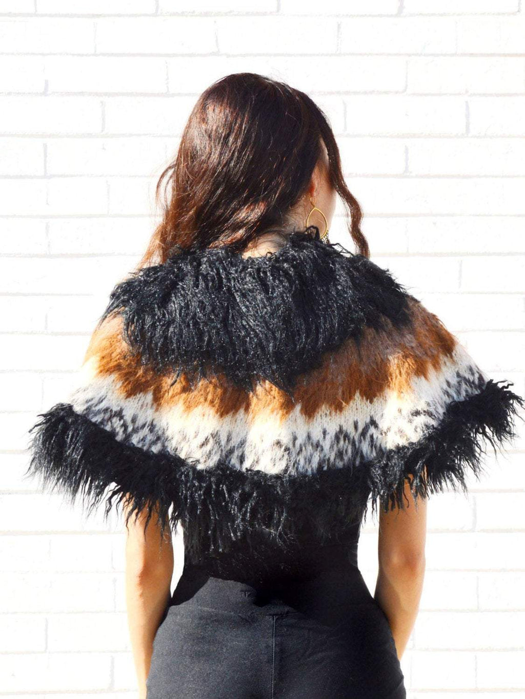 Woman facing white brick wall wearing a faux fur, brown, white, and black capelet.