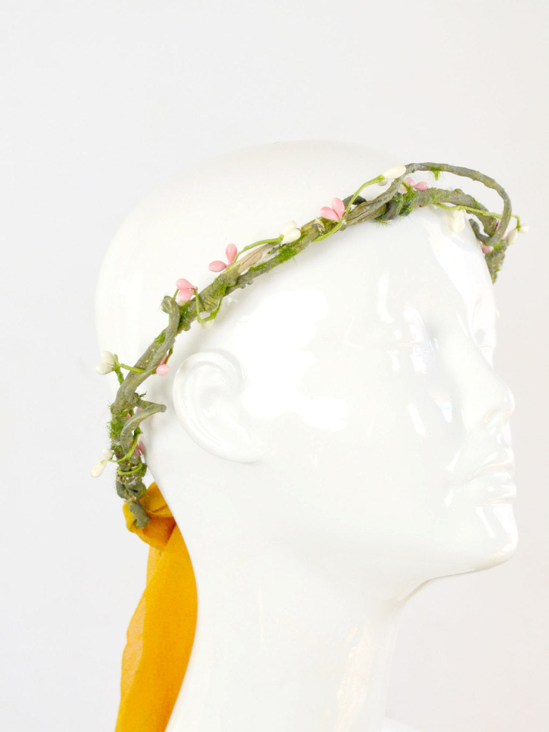 Mannequin head wearing a green, yellow, and pink crown of branches with a yellow tie.