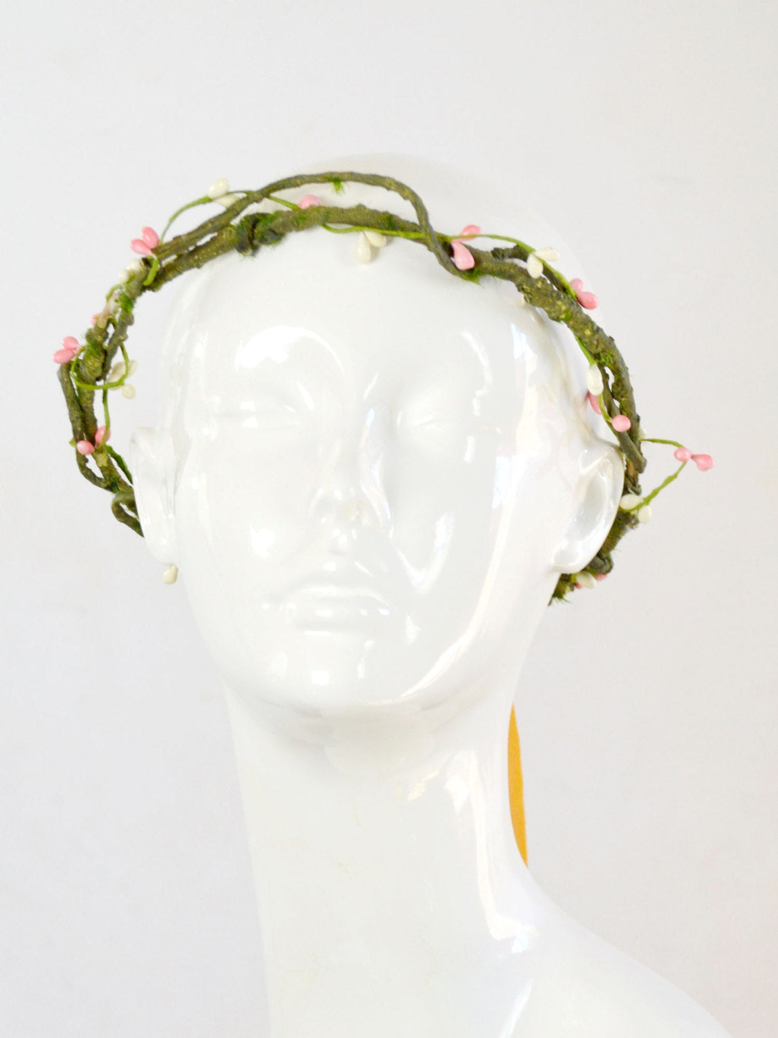 Mannequin wearing a crown of green branches and vines, pink flowers, yellow flowers, silk tie.