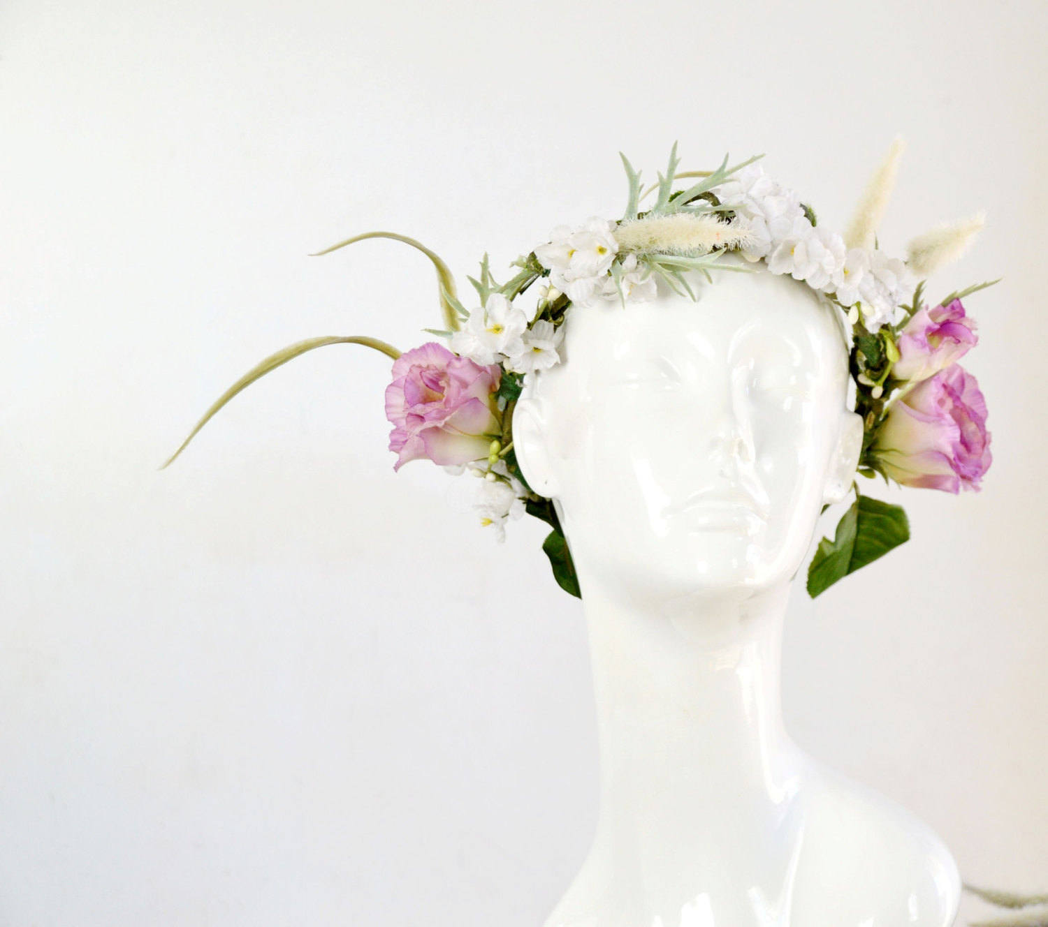 bridal head piece with pink flowers, green leaves, stems, and vines
