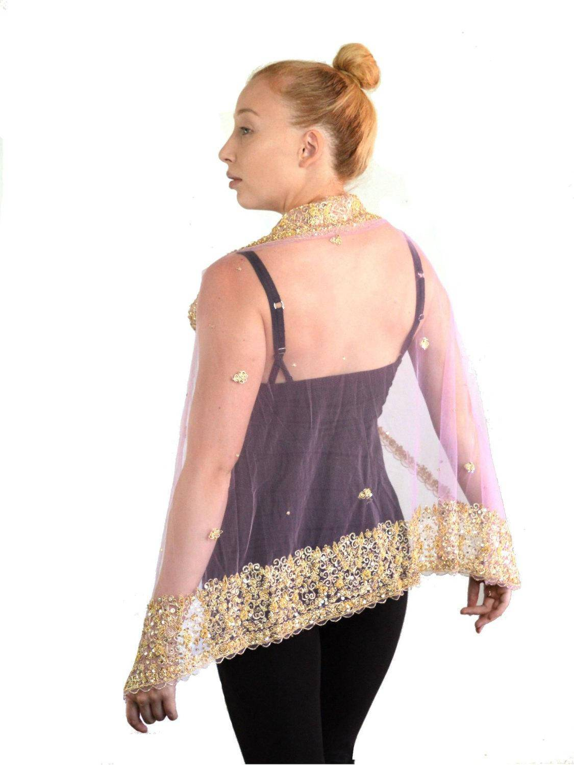 Woman with hair in bun wearing a pink and gold net bridal cape.
