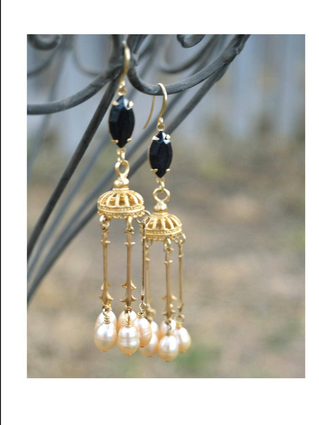 Long, gold chandelier earrings with black gemstones and ivory pearls.