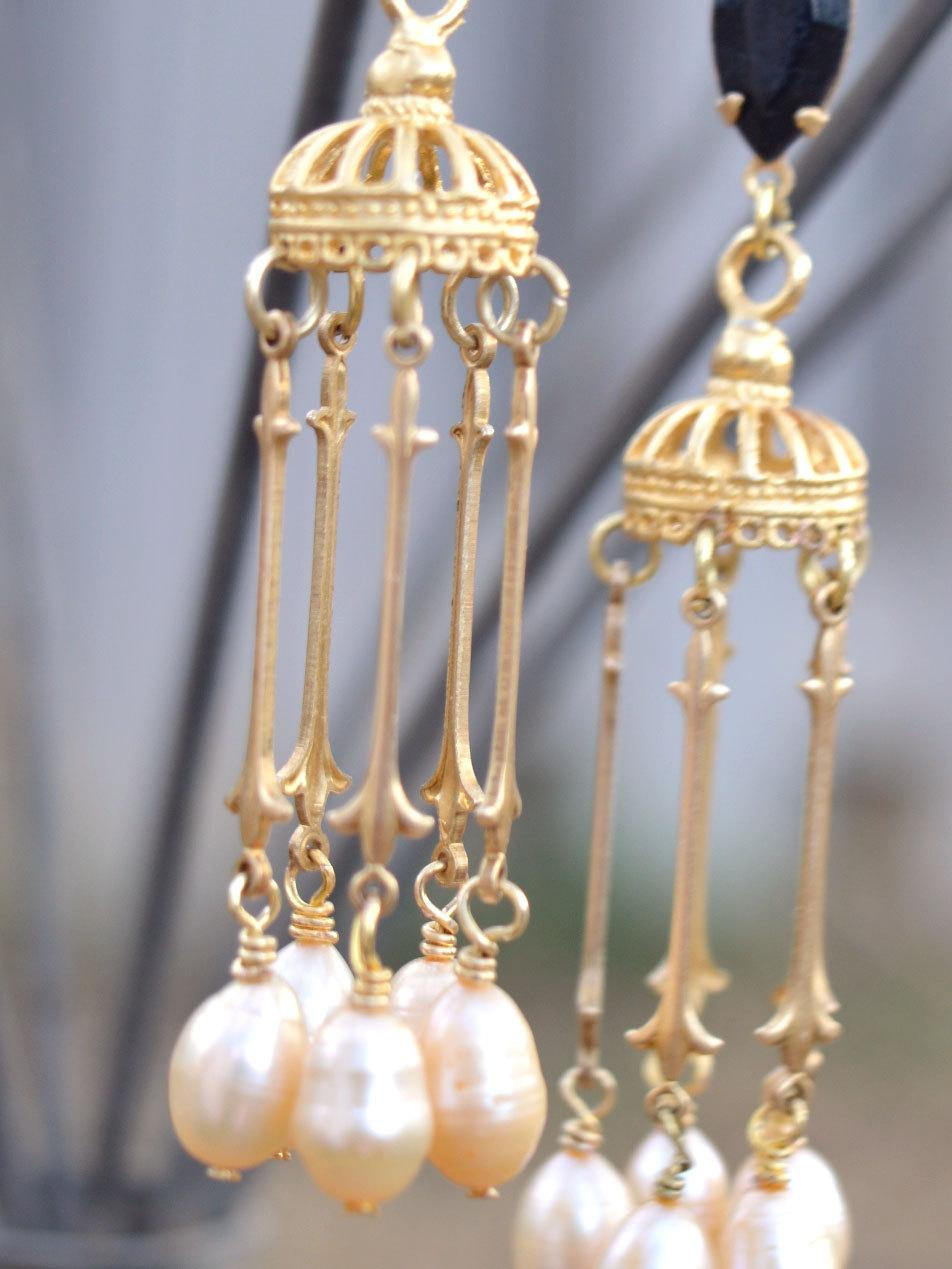 Gold chandelier earrings with long pearl drops and black crystals.