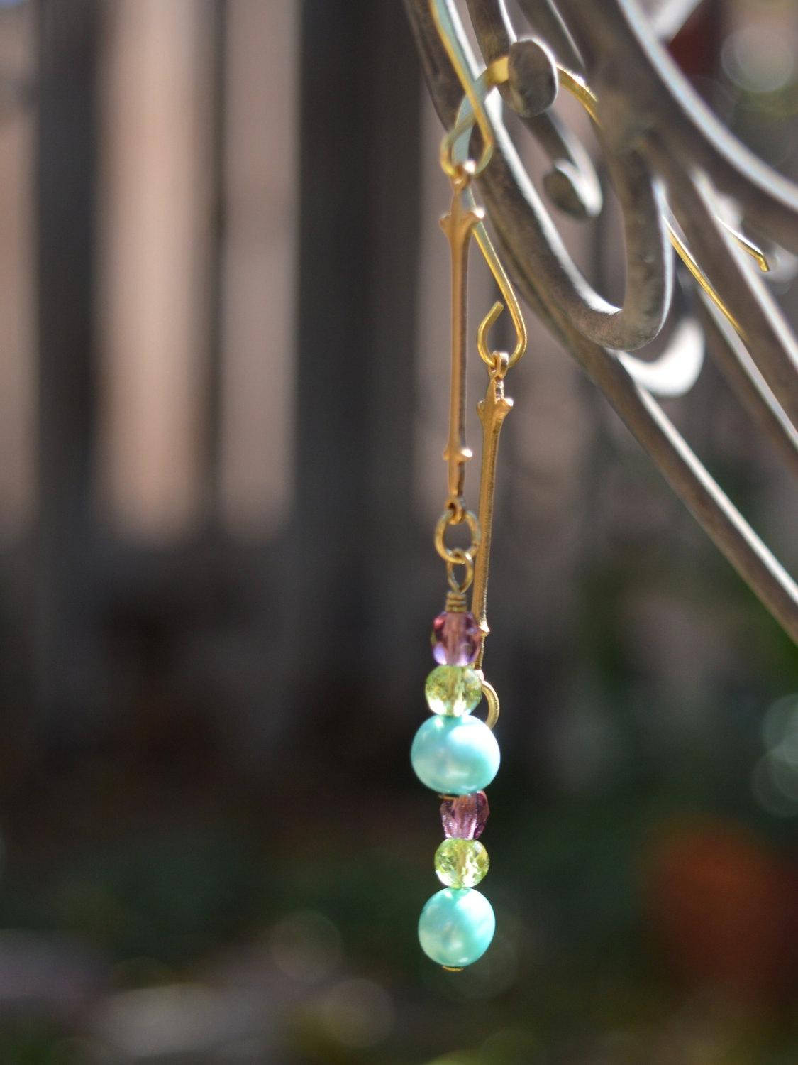 Gold drop bridal earrings with blue freshwater pearl, peridot gemstone, and brass fleur de lis.