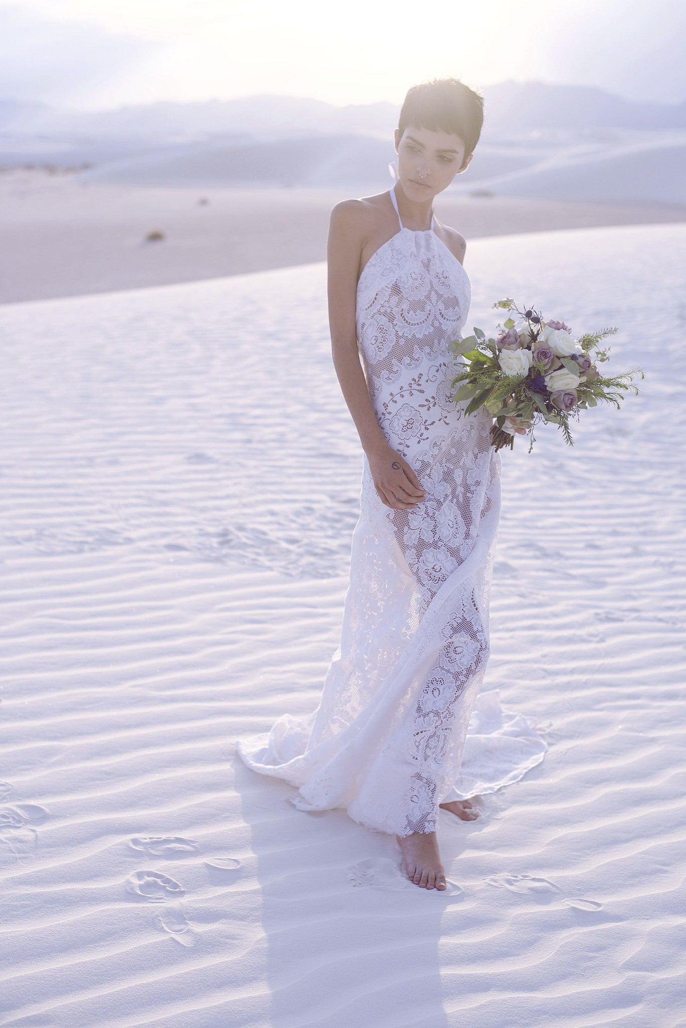 bride in white sands wearing long white cotton lace wedding gown with chapel train.
