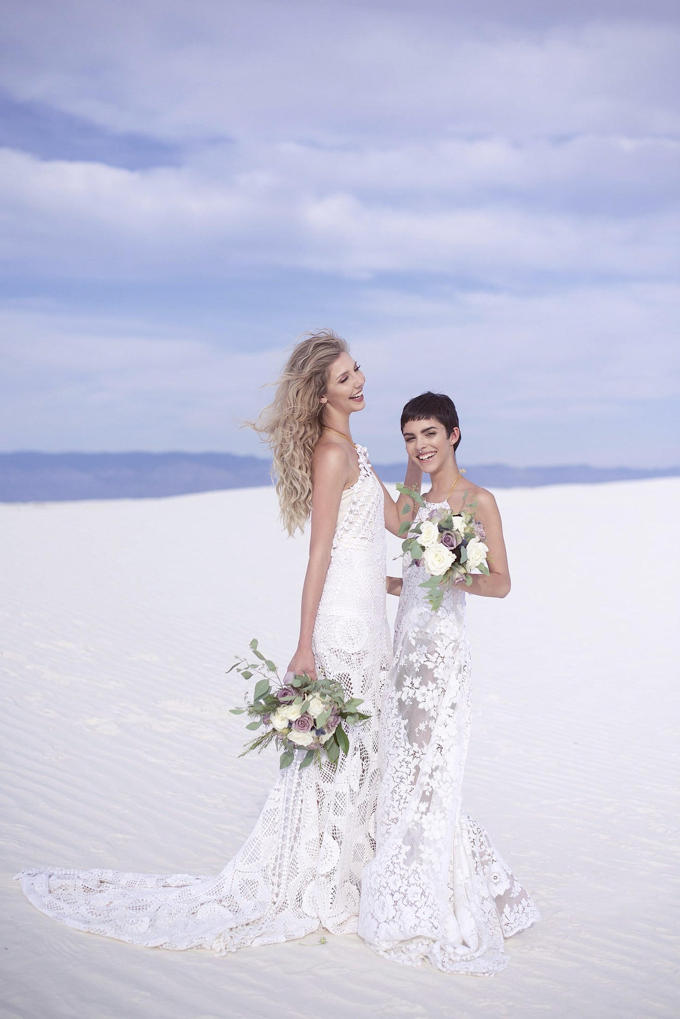 Two brides wearing long lace crochet wedding gowns with trains.