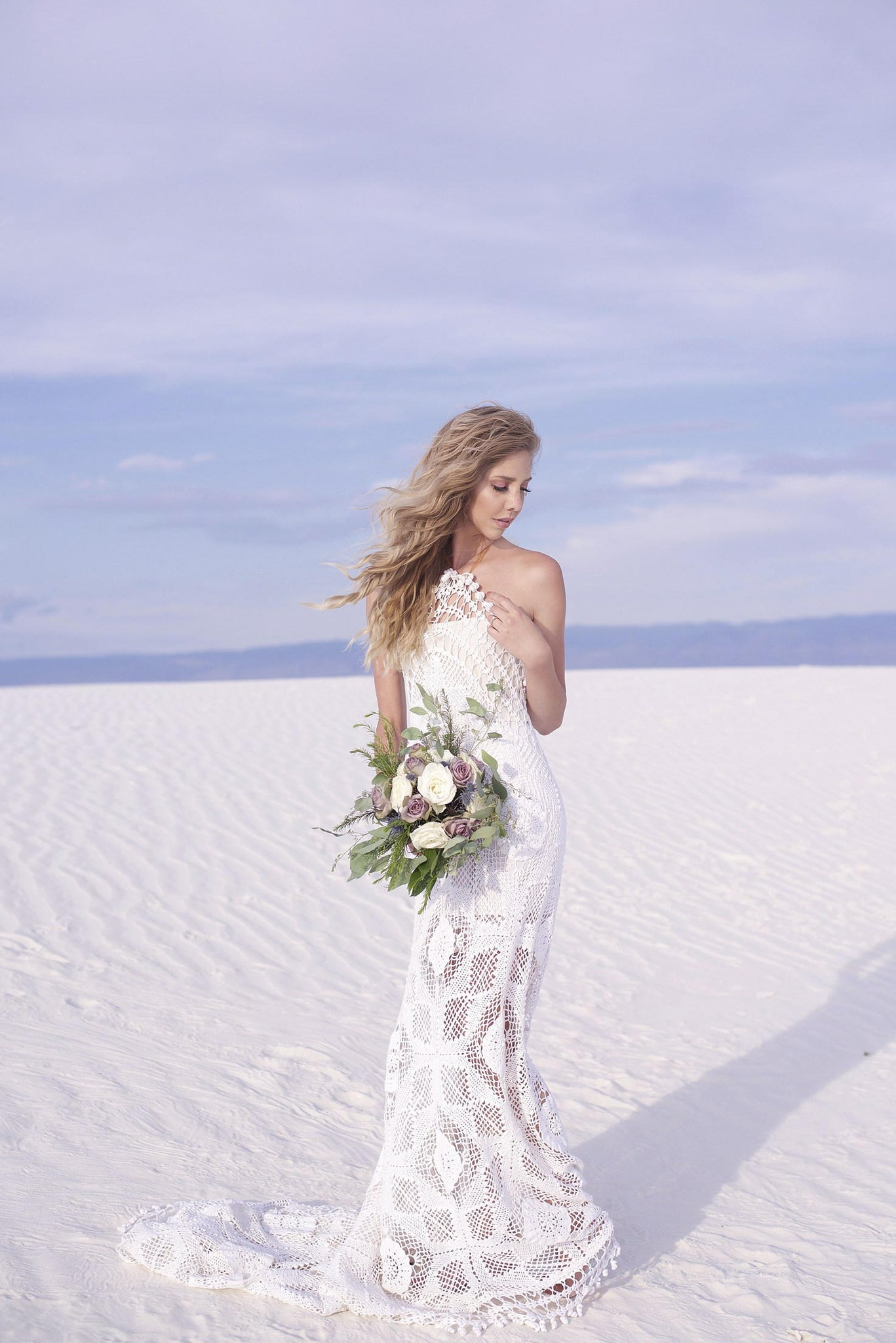 Beautiful blonde bride wearing long white crochet wedding gown with train.