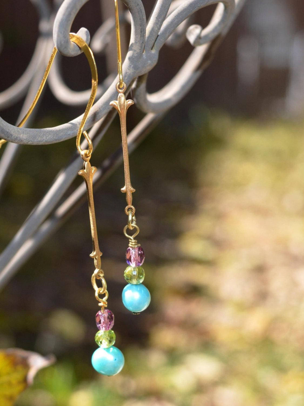 Long gold earrings with blue freshwater pearl, green peridot bead, and purple crystal.