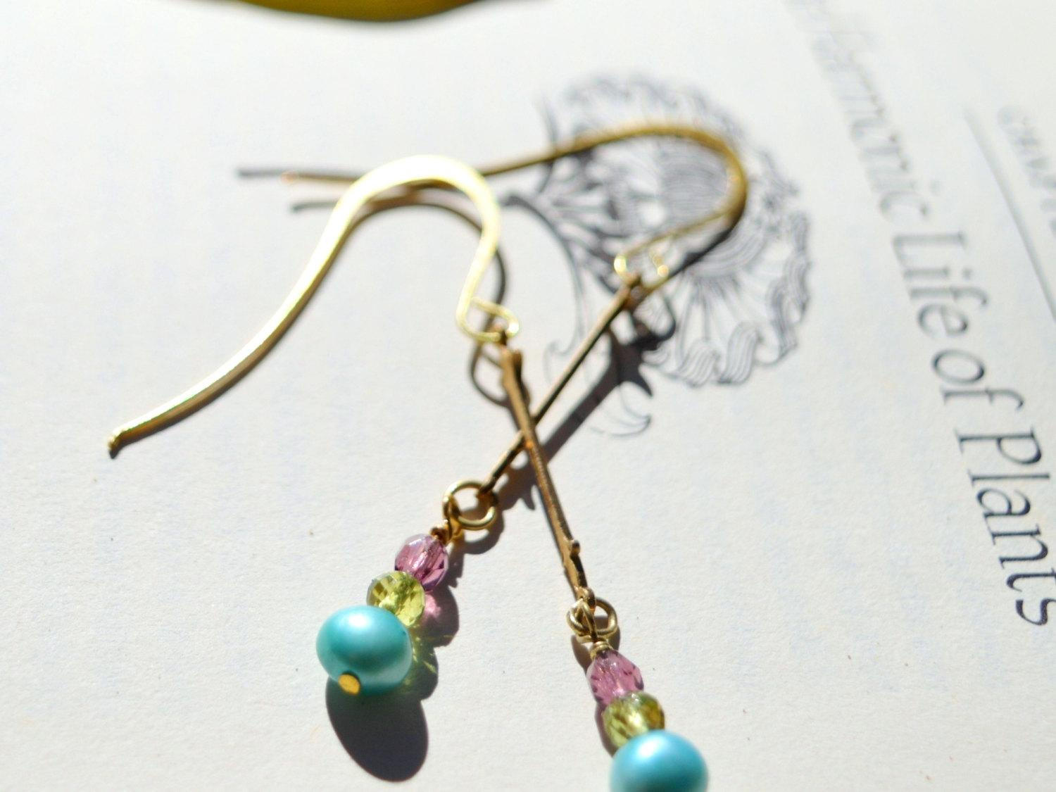 Long gold earrings with blue pearl, peridot, brass fleur de lis.