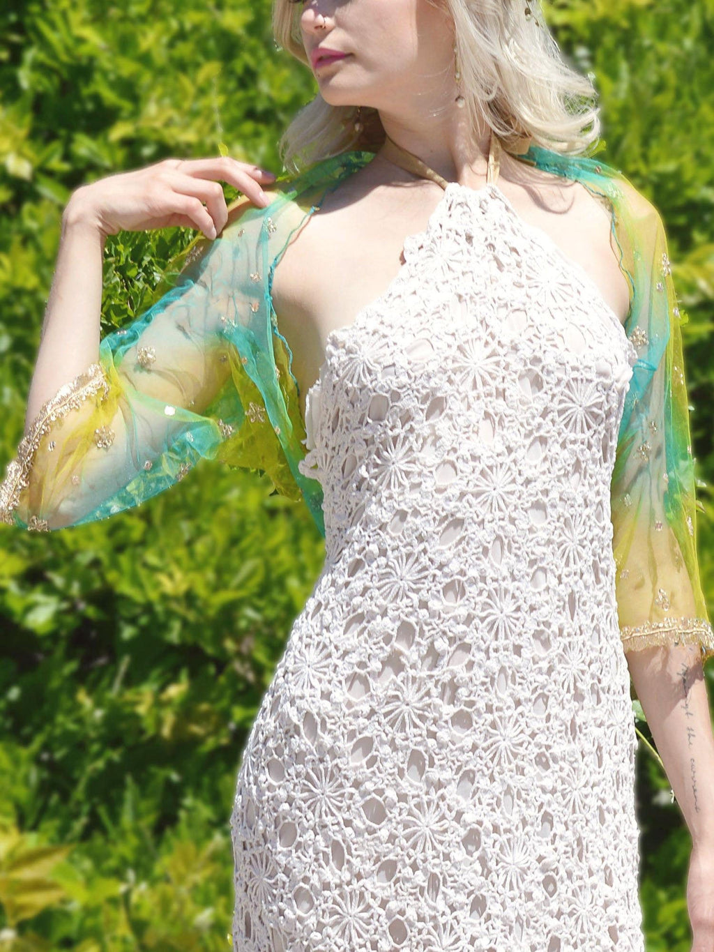 blonde bride in white crochet wedding dress and yellow and blue shrug.
