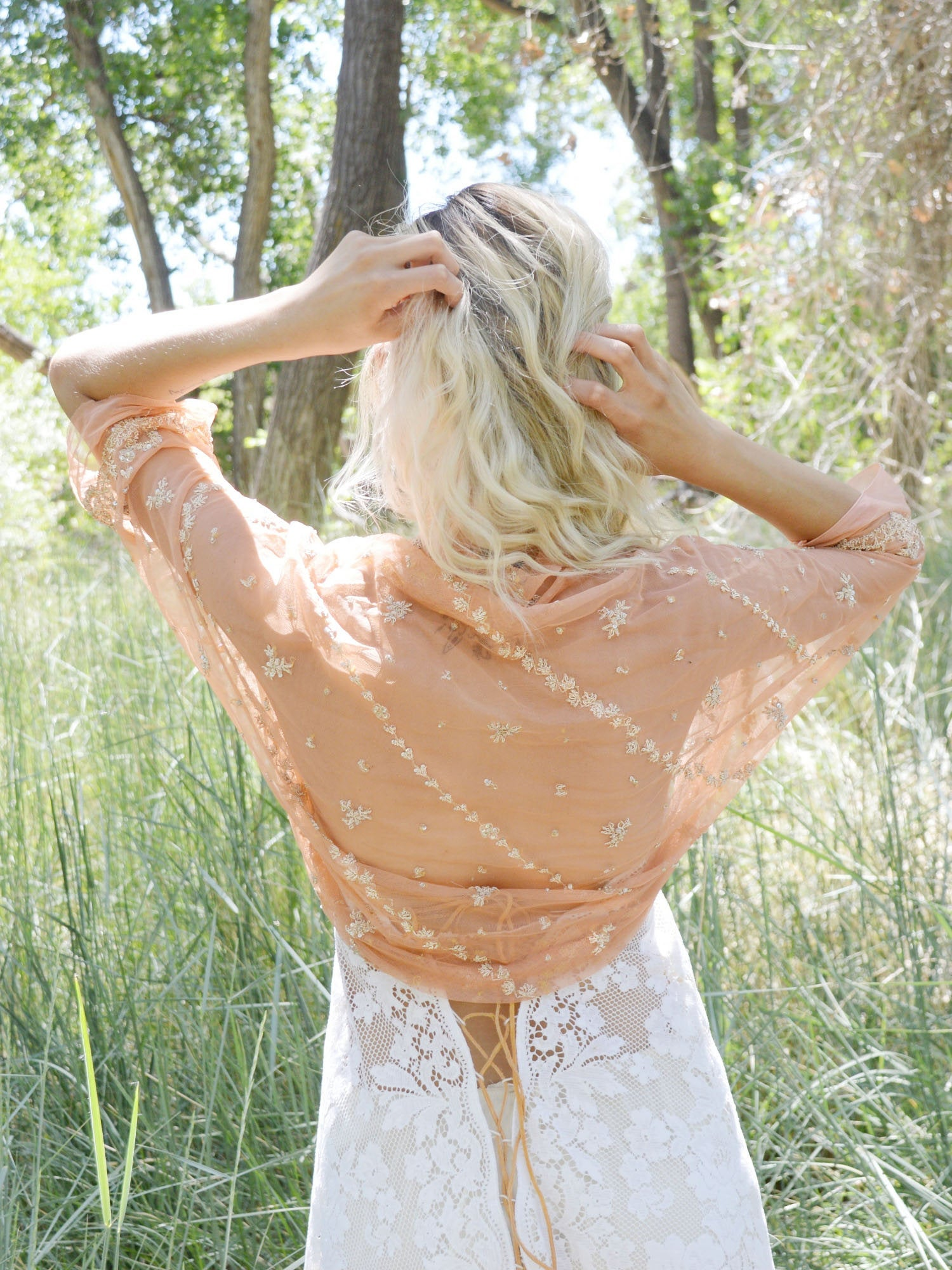 blonde bride with peach and gold wedding jacket