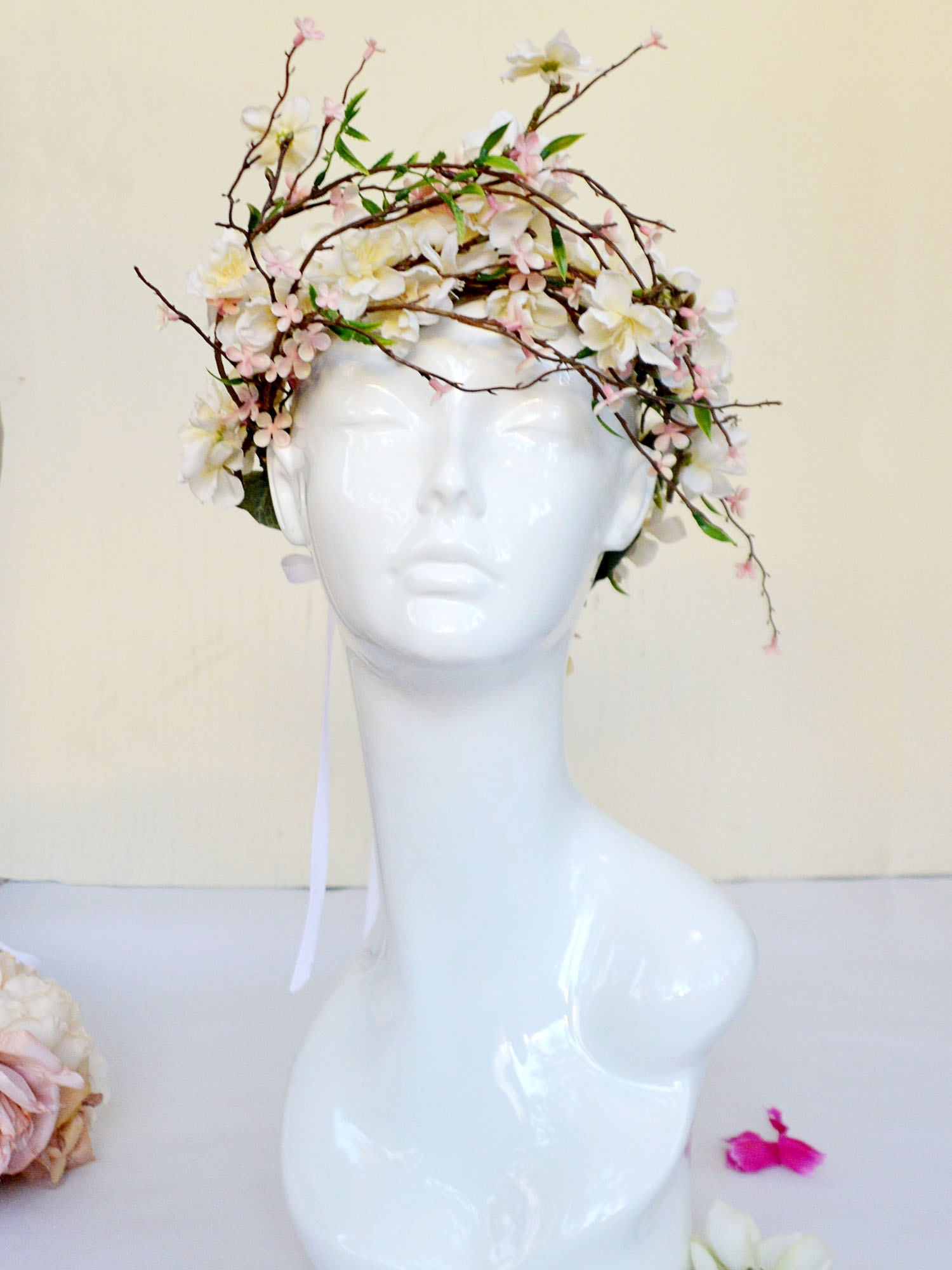 White mannequin head wearing a wedding crown of cherry blossoms.