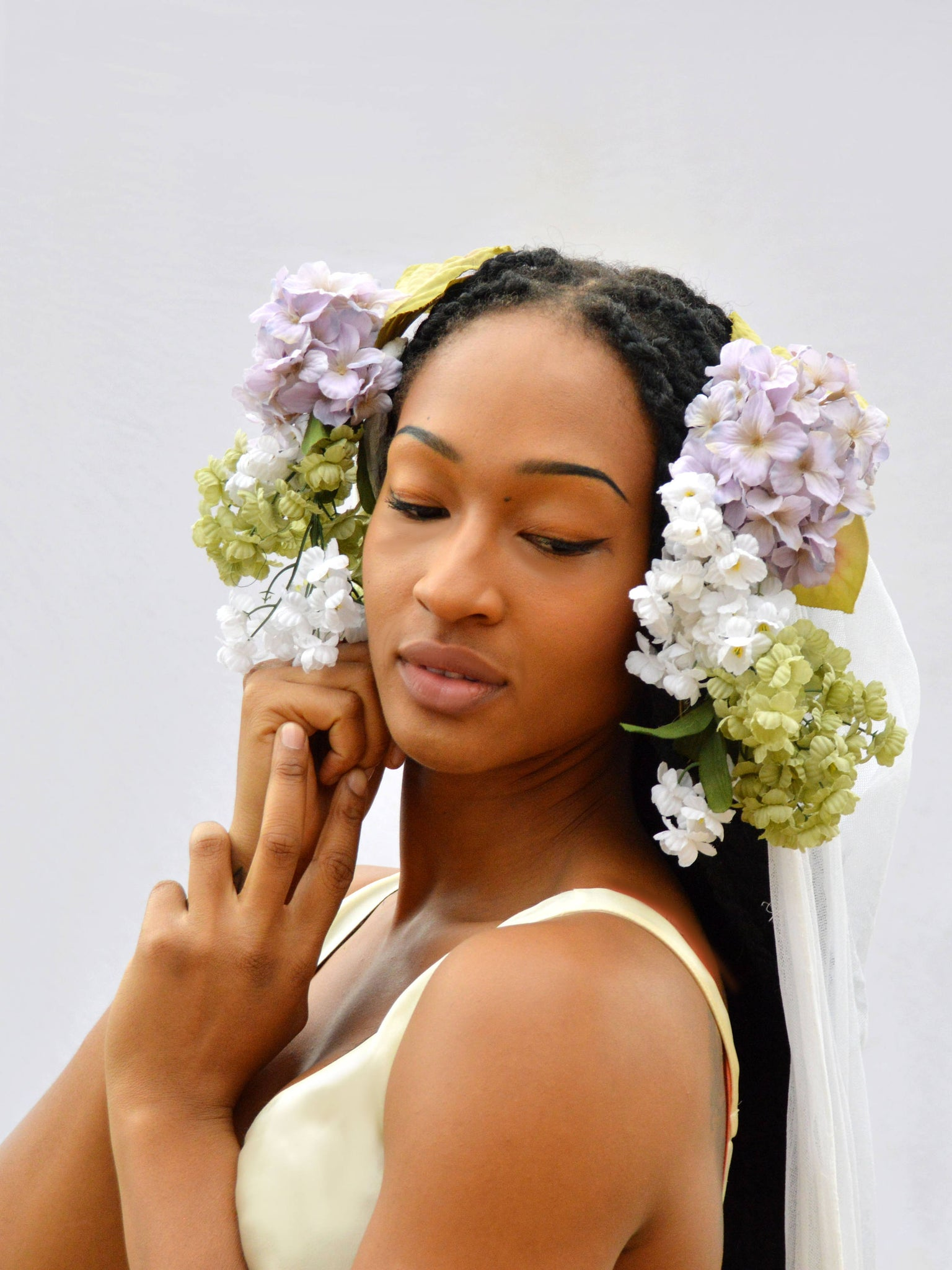 close up of model in white wedding dress, with purple, green, and white flowers in her hair.
