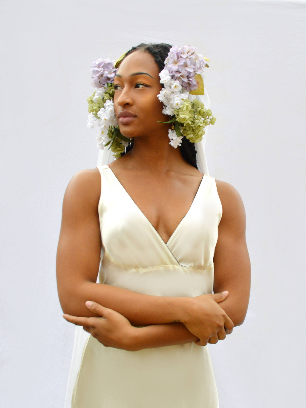 beautiful model in white wedding dress and purple and green flower crown veil