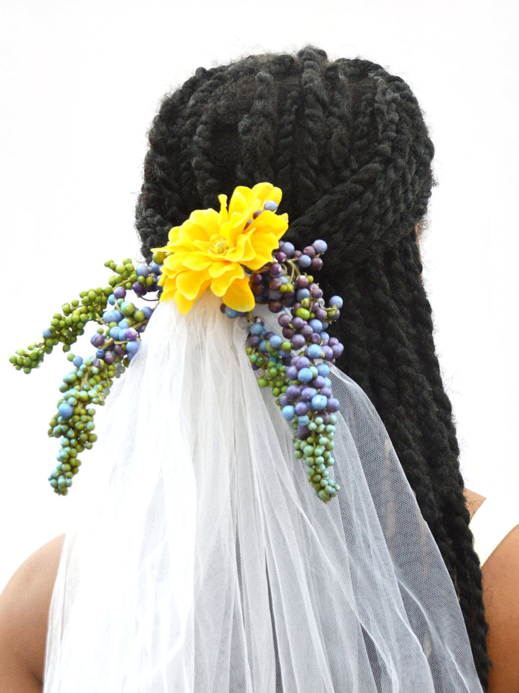 Bride wearing a floral clip veil in white, yellow, green, and purple.