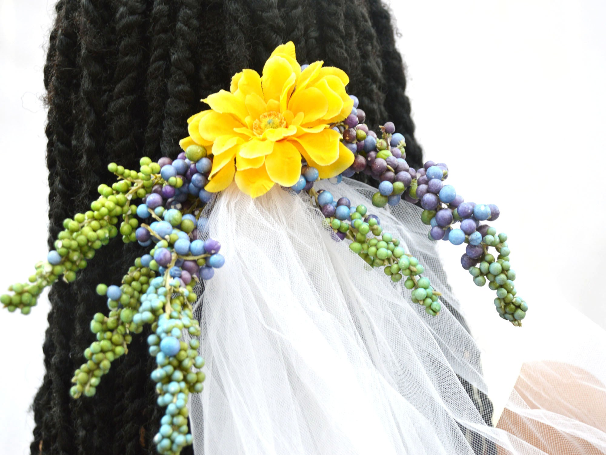 Wedding clip veil with green, yellow, and purple flowers.