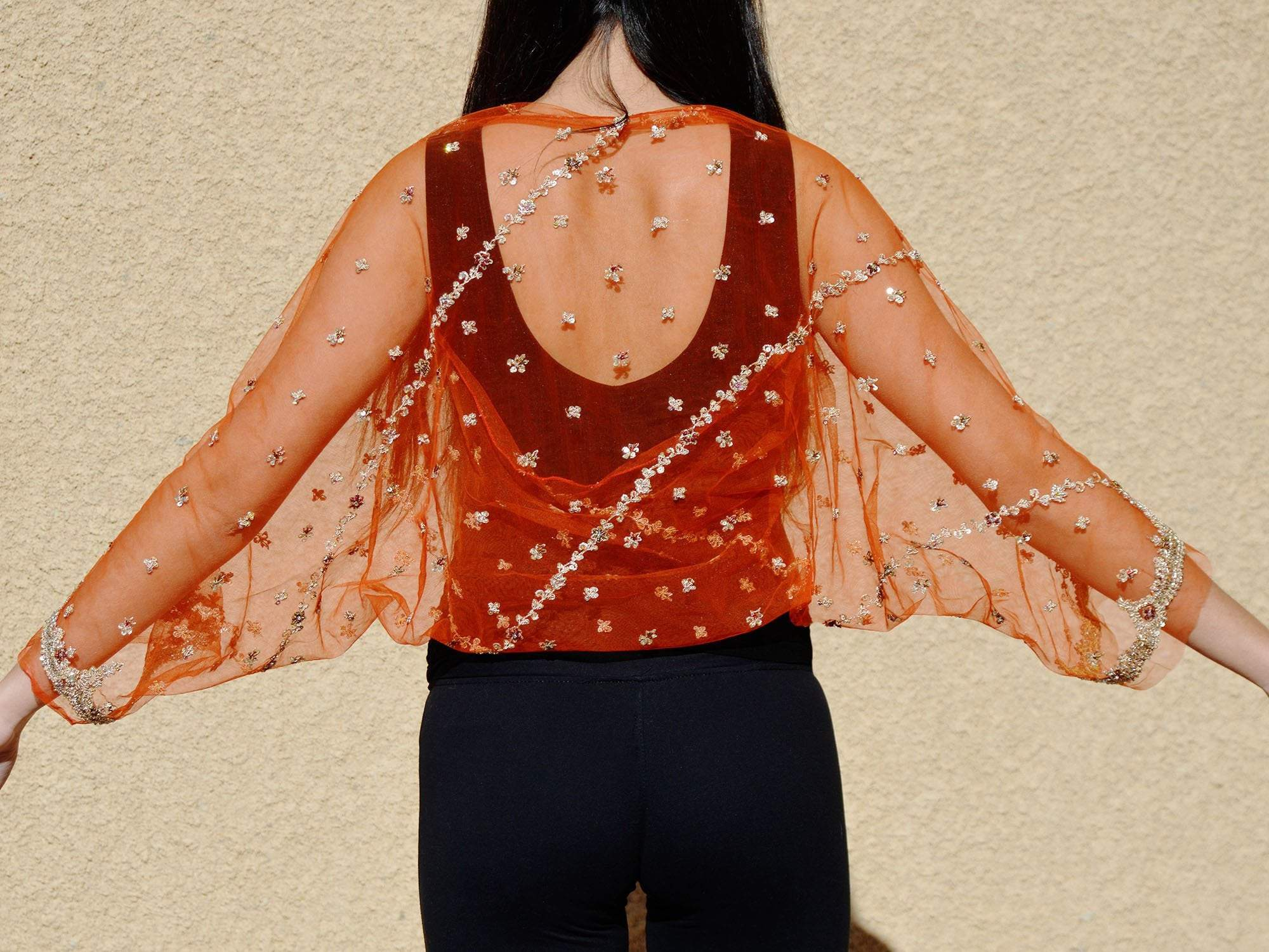 Back view of woman wearing a sheer orange bridal shrug jacket with gold beads.