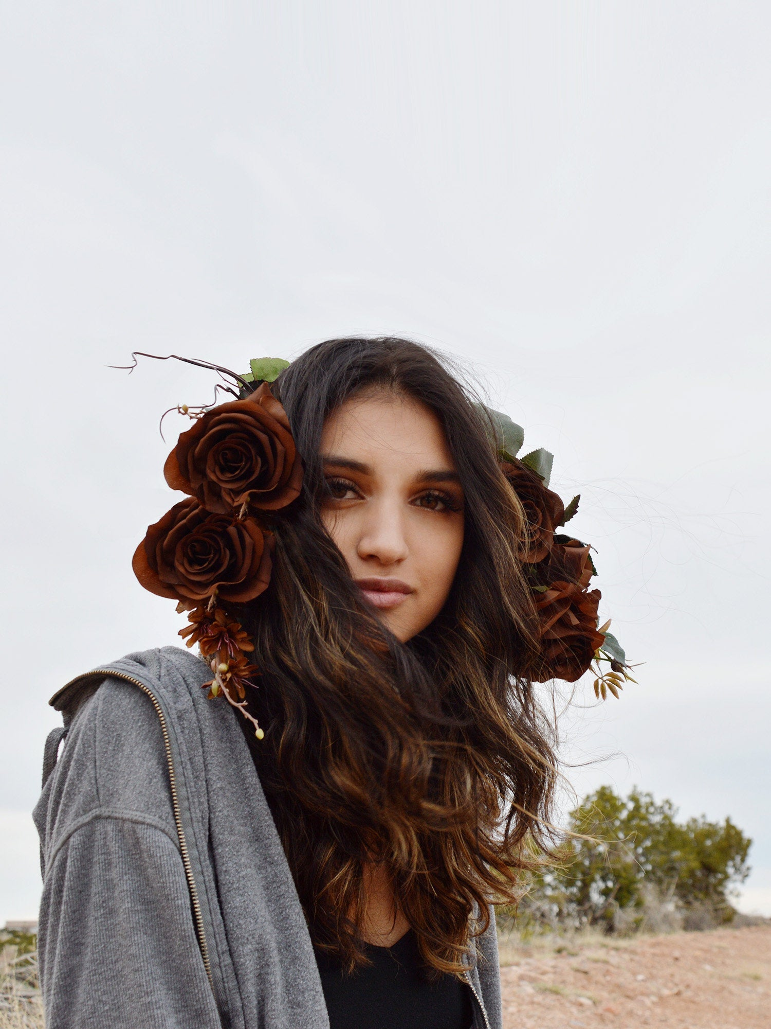 Bohemian woman wearing brown rose flower crown with green leaves and branches.