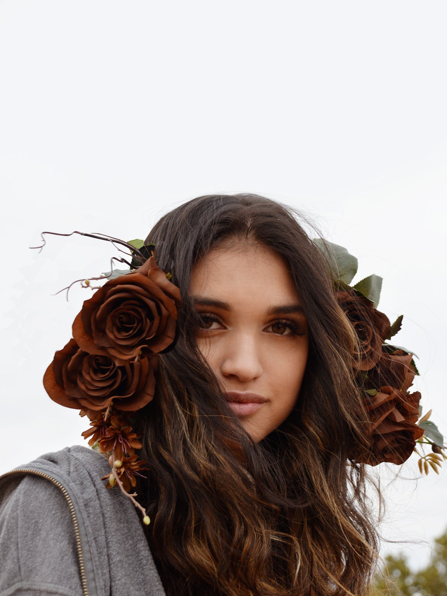 Woman wearing bohemian flower crown with brown roses.