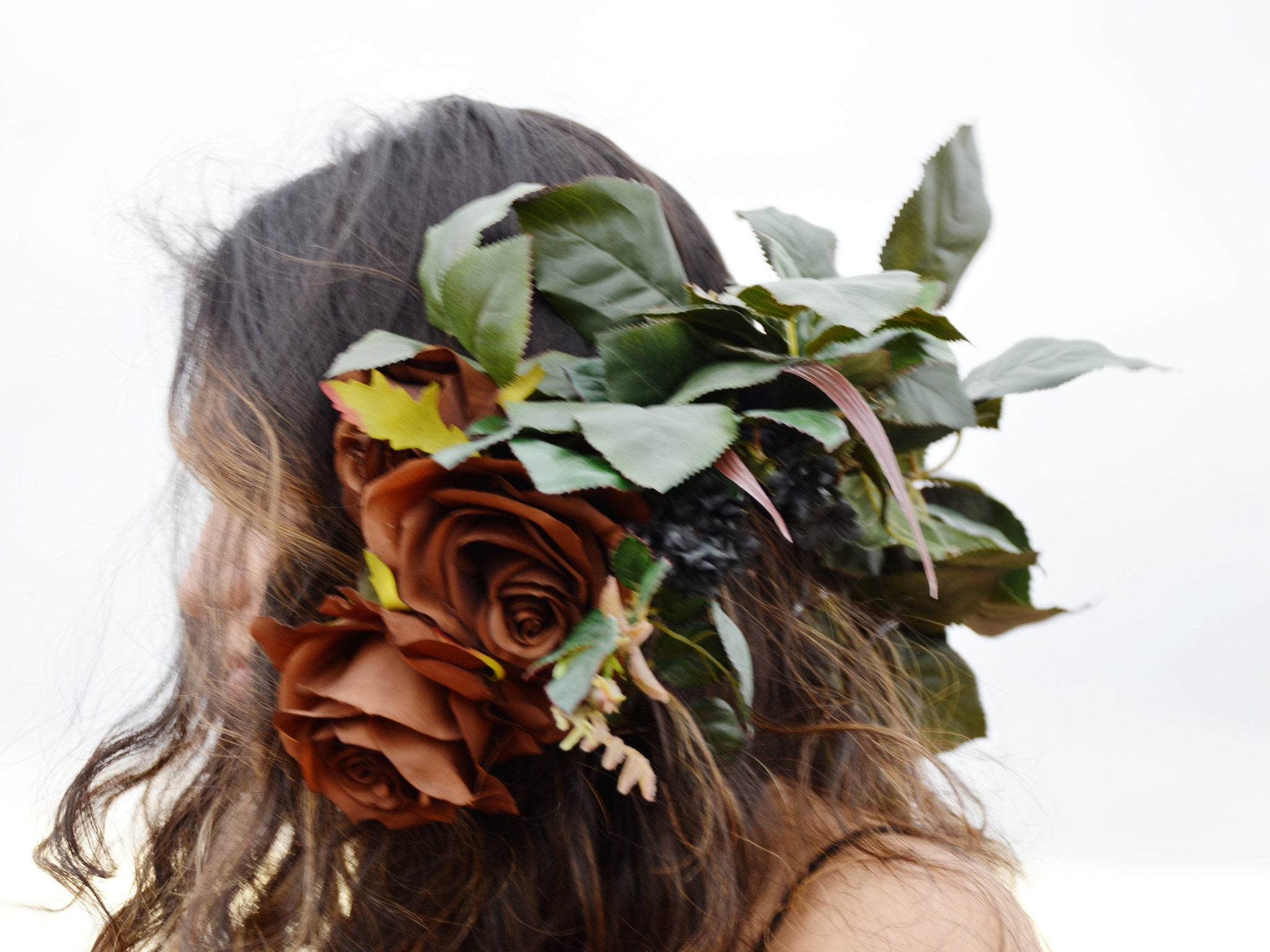 Woman wearing brown roses floral crown with green leaves.