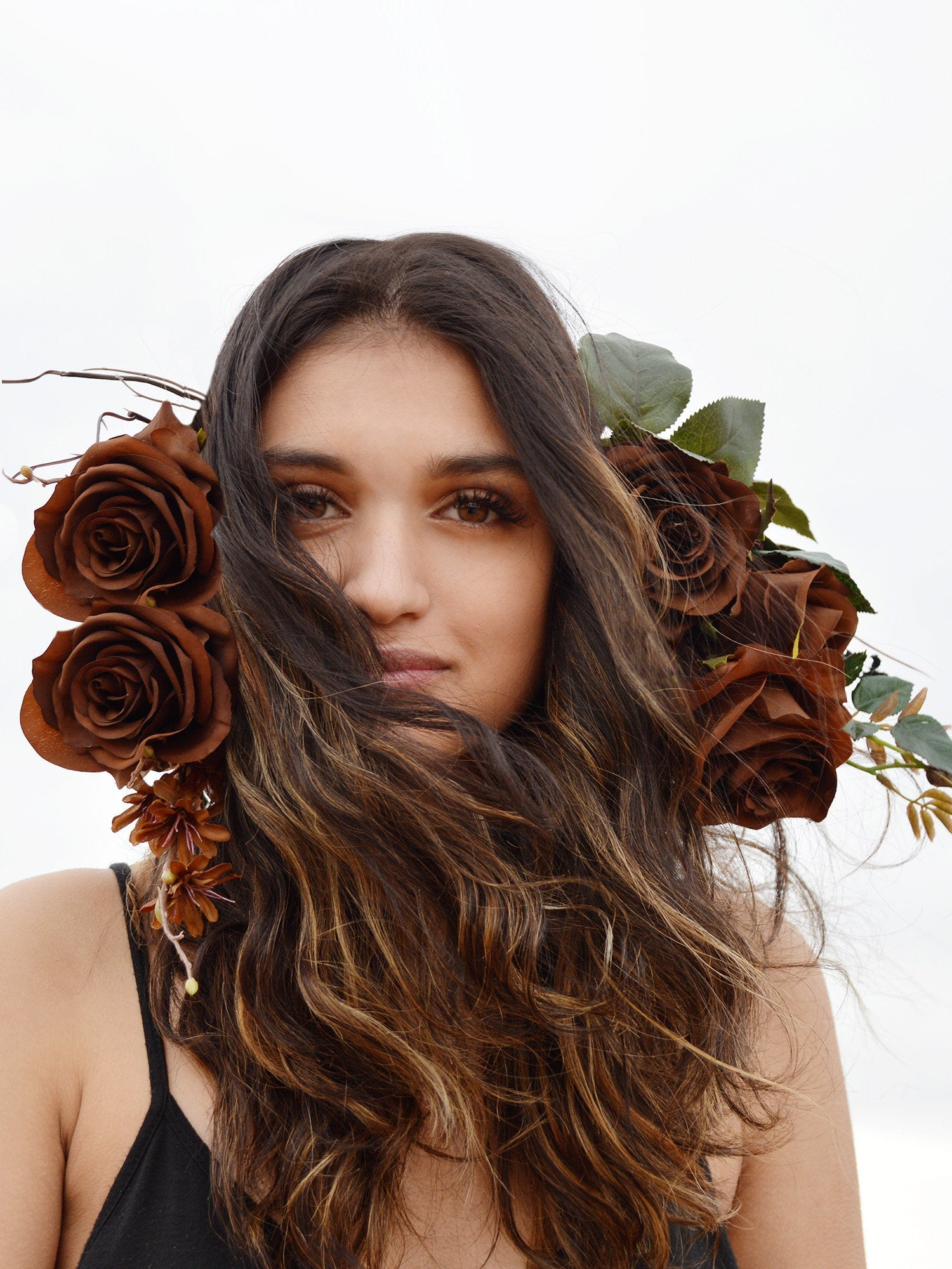 Brunette model wearing bridal flower crown with brown roses, branches, and leaves.