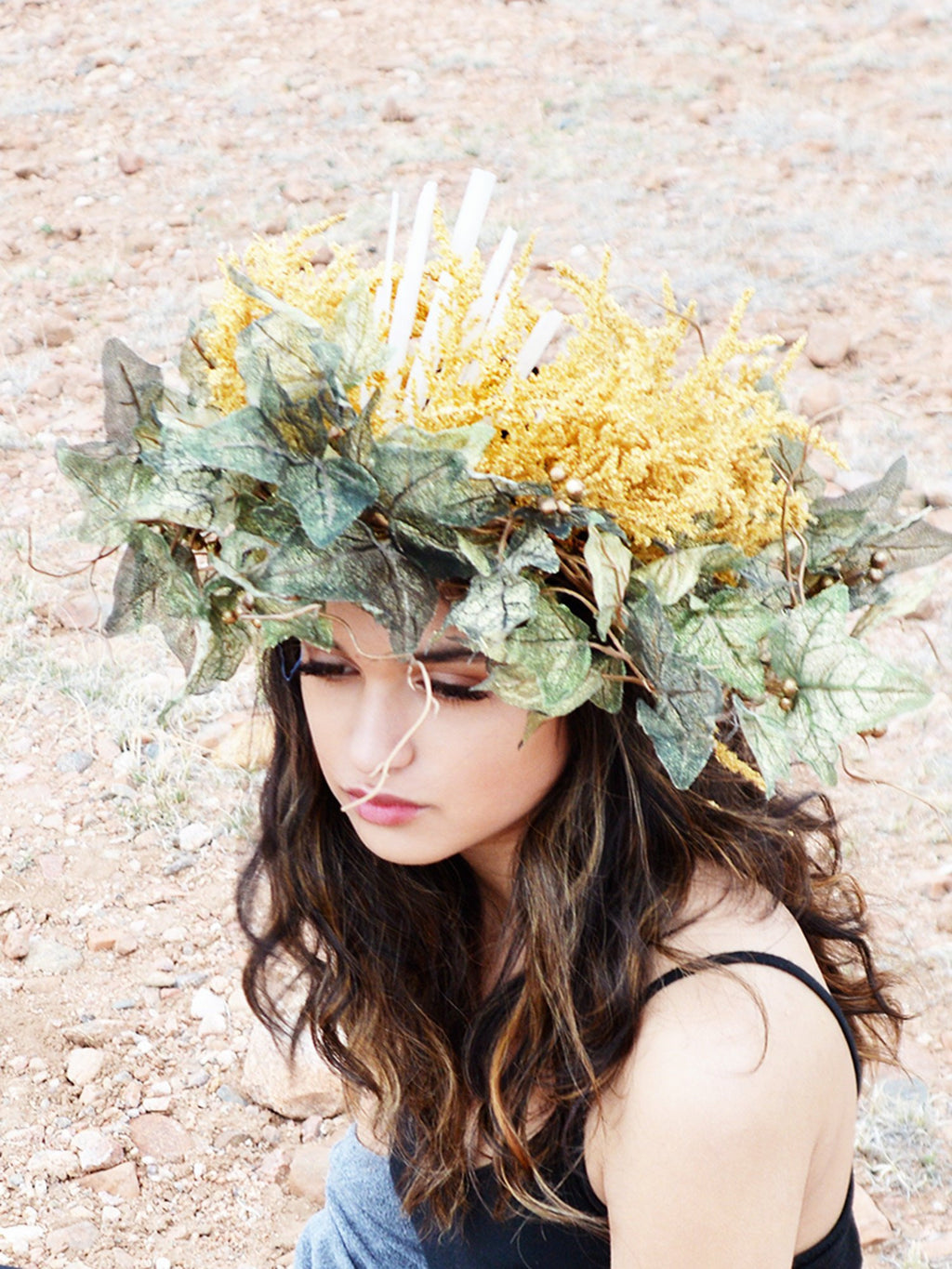 Brunette woman wearing green and gold flower crown with crystal spikes.