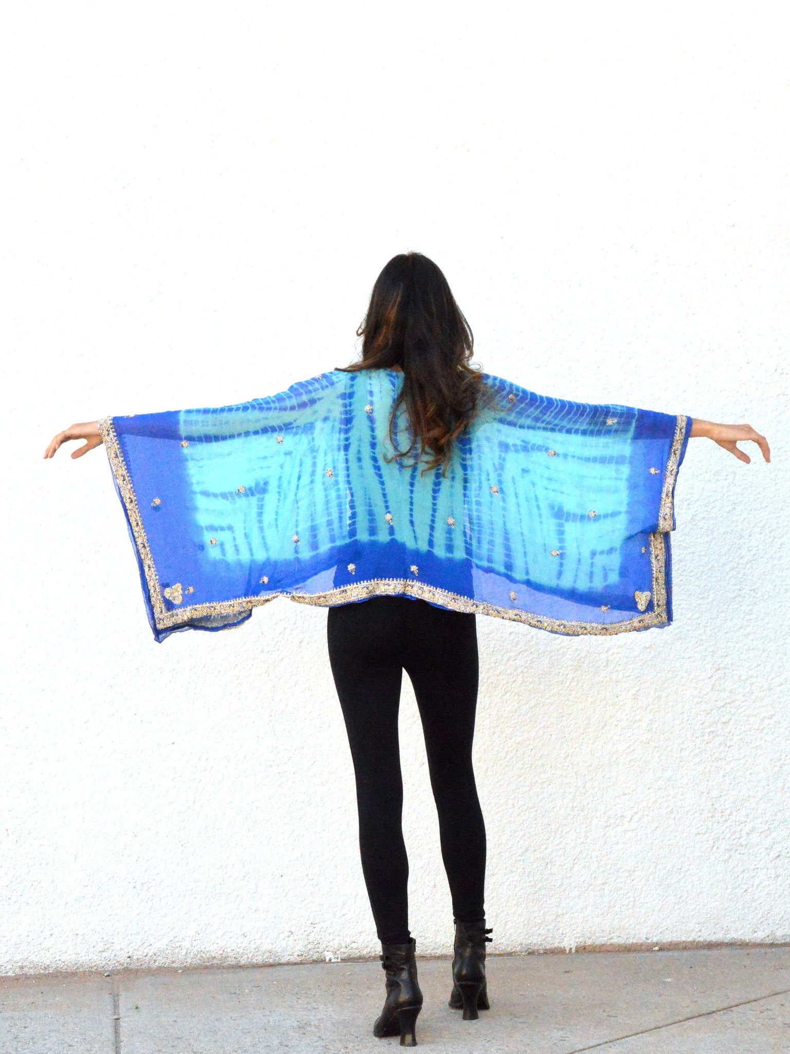 Back view of woman with arms outspread, wearing blue silk cropped kimono jacket.