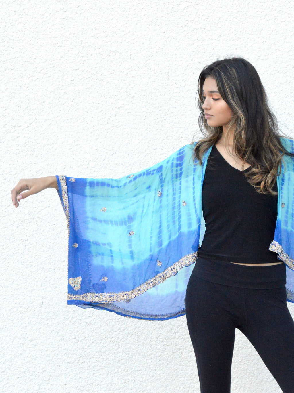 Model wearing tie dyed blue silk cropped kimono jacket with silver embroidery.