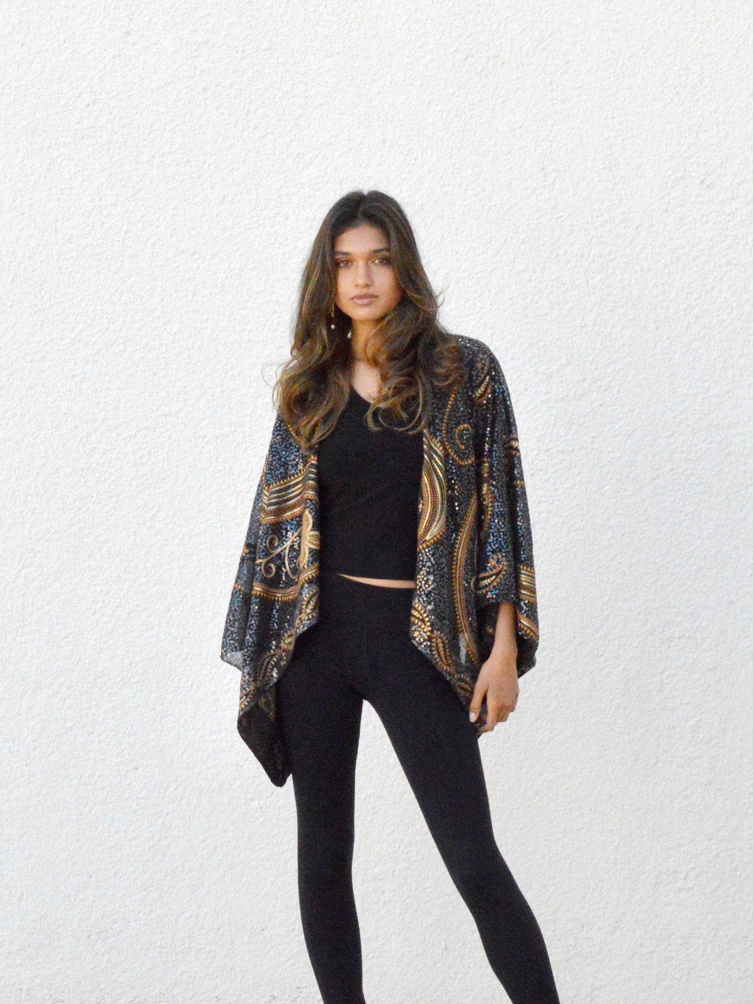 Dark haired woman in black crop kimono jacket with gold sequins.