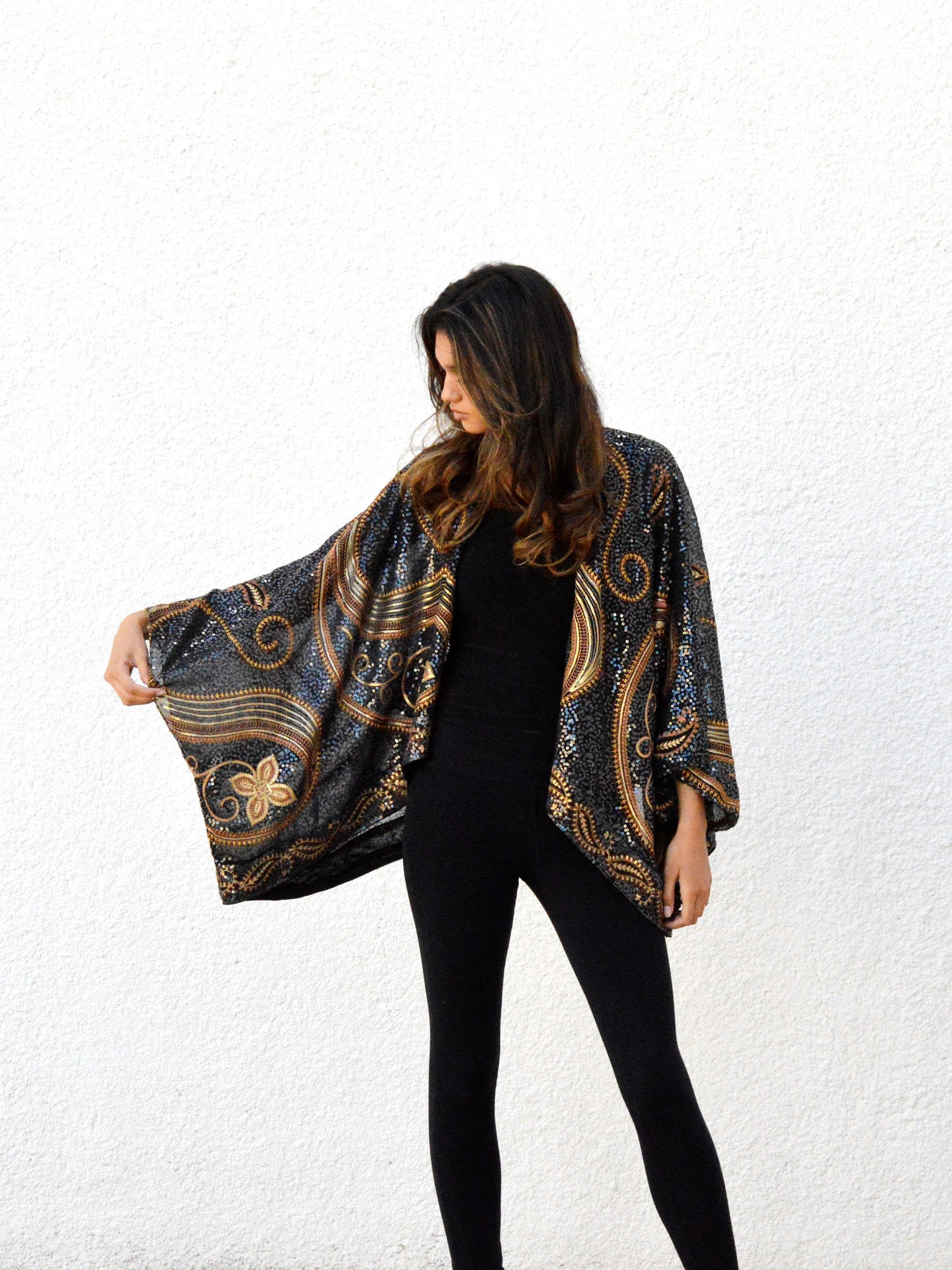 Woman in short kimono jacket with black and gold paisley sequins.