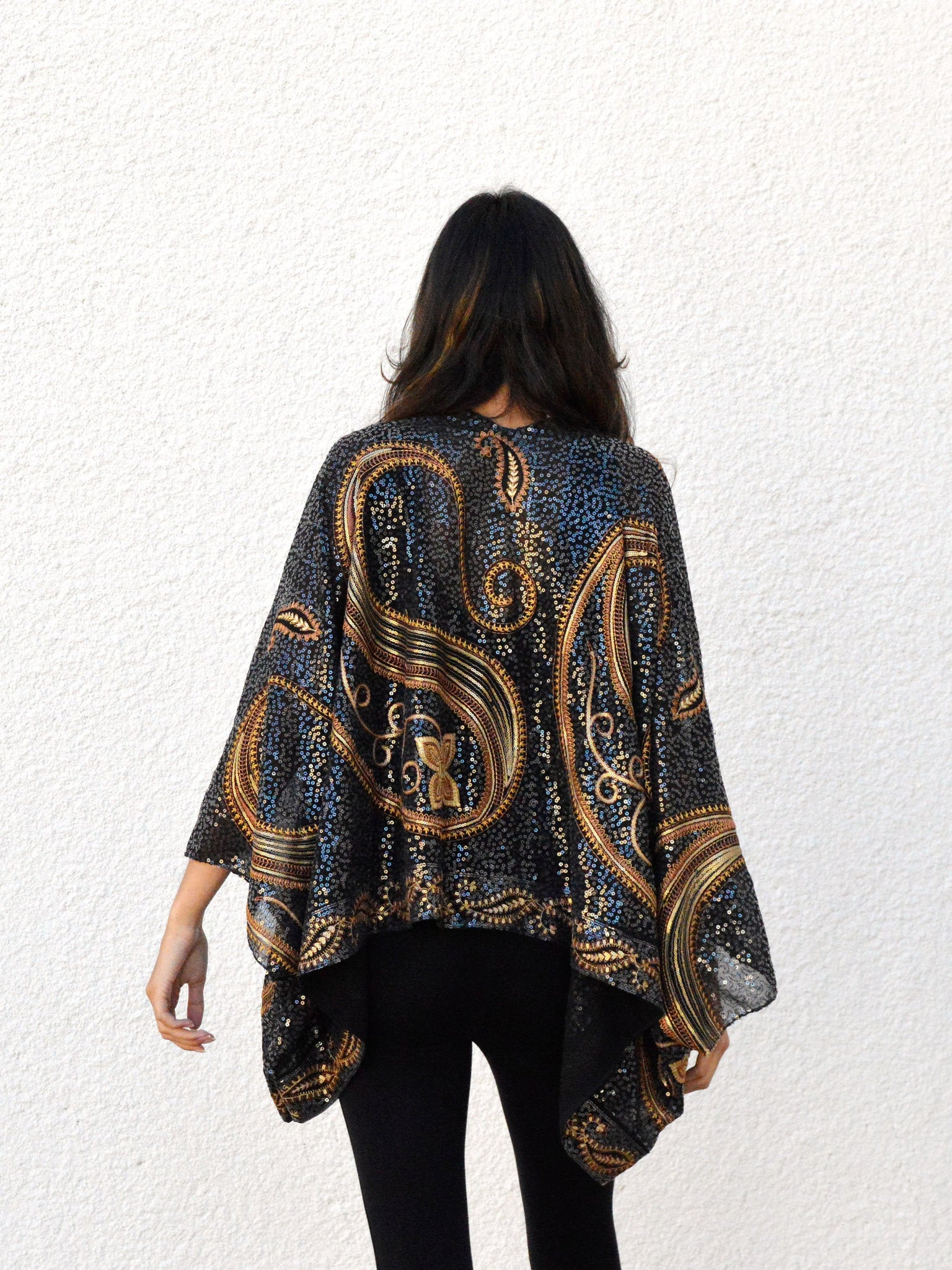 Back view of a model wearing a sequin kimono jacket with black and gold paisley designs.
