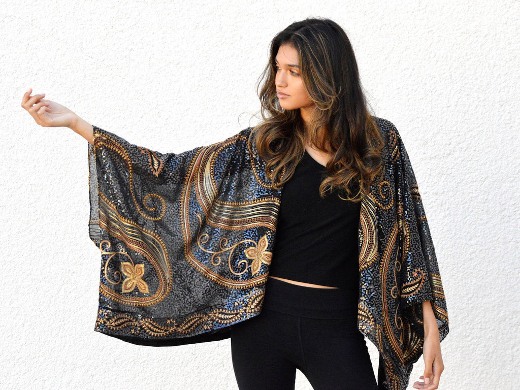 Brunette model wearing a black and gold paisley sequin jacket.
