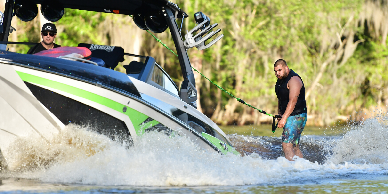 man holding rope wakesurfing behind boat