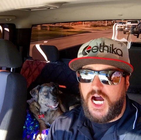 man and dog riding in truck to go wakesurfing
