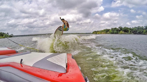 doomswell brand ambassador wakesurfing behind red boat on a neo wakesurf board