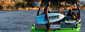 man with doomswell wakesurf board on boat
