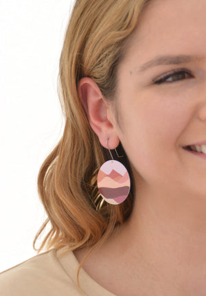 This is an image of a woman wearing a Kitty Came Home earring in her left ear. The flat circle is 36 millimetres in diameter and hangs from a shepherds hook. The design is lily of the valley by Satin and Tat. A landscape of magenta, burgundy and dusty pink hills lies beneath a pale pink sky.