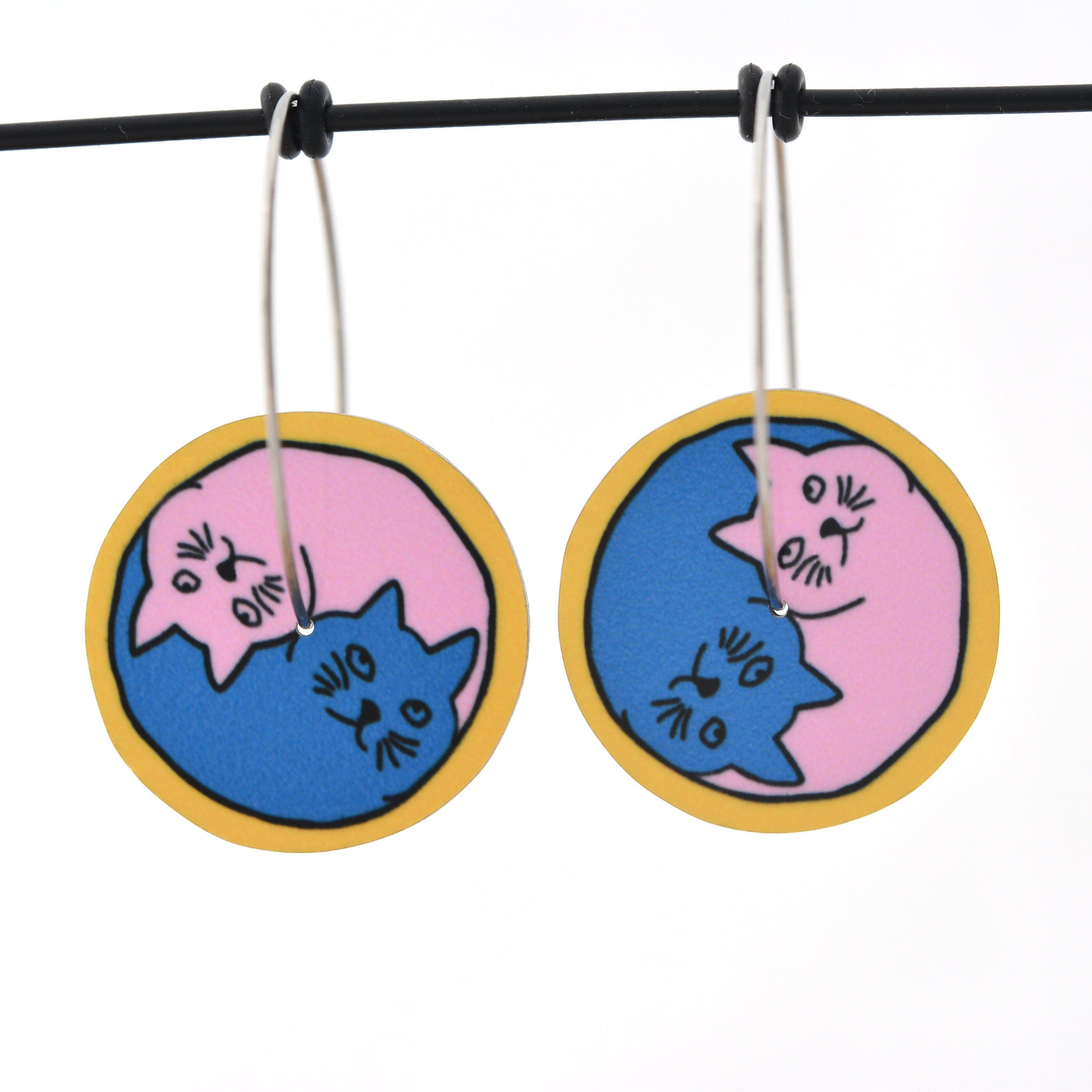 Yin Yang Cats circle earrings in pink and blue with a yellow outer edge, approximately 24mm round. Aluminium, with surgical stainless steel hoops approximately 30mm in diameter.