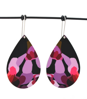 Droplet earrings featuring pink Geraldton Wax flowers on a black background. The aluminium droplets are approximately 40mm long and 29mm wide. The 15mm long shepherds hooks are surgical stainless steel.